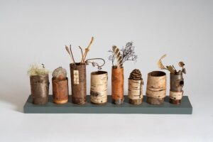 Row of 'Collecting Pots' on wooden base Ht 13 x wdth 47 x dpth 10 cms £120.00
